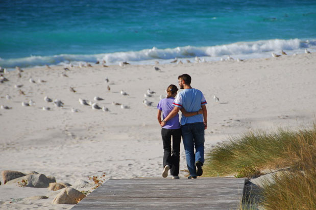 photo of couple with arms around each other going to beach
